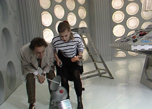 A Delivery Bot materializes in the TARDIS console room, spamming the Doctor and Ace with junk mail (c) BBC Studios