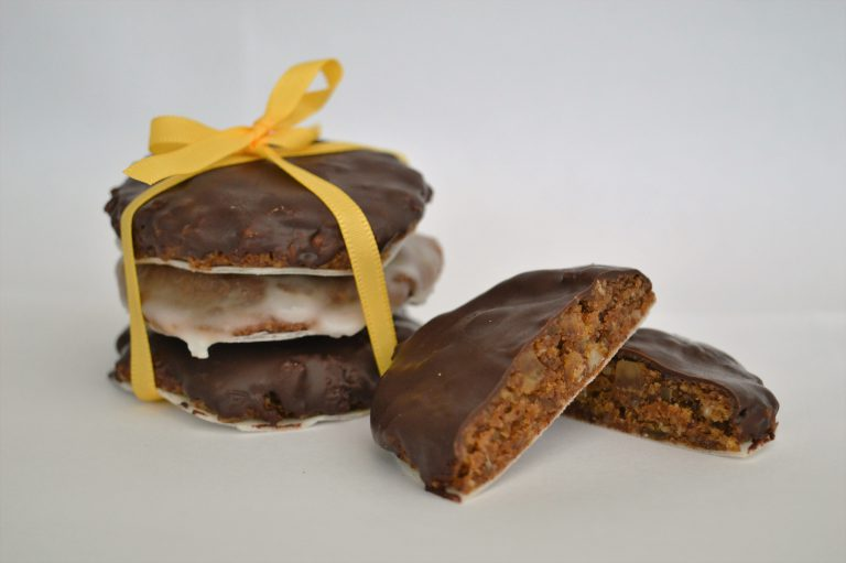 Authentic Elisen-Lebkuchen covered in chocolate and icing stacked on top of each other. Tied together with a yellow ribbon.