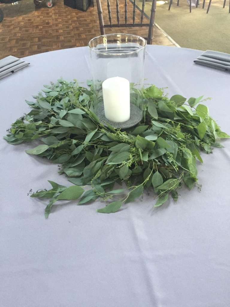 Garland of greens around a hurricane or cylinder with pillar candle