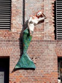 Meerjungfrau an einer Häuserwand im Hafen
