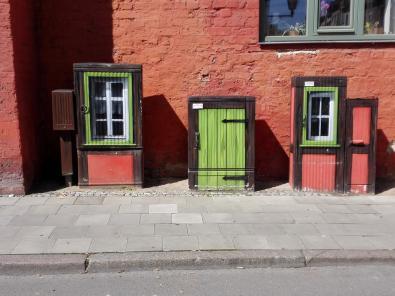 Hübsch bemalte Stromkästen an einer Hausfassade