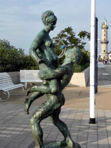 Skulptur auf der Strandpromenade, dahinter der alte Leuchtturm