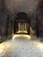 Ein langer dunkler Gang als Zuweg hinter dem Festungsportal
