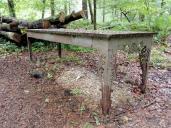 Kunstwerk im Wald als Symbol für die Trennung von Arm (einfache hölzerne Tischbeine, links) und Reich (aufwändig gearbeitete metallene Tischbeine, rechts)