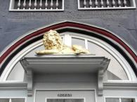 Hier wacht ein Löwe über die ein- und ausgehenden Besucher