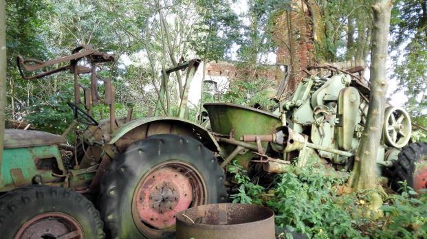 Neben einer Ruine mitten in der Landschaft rosten alte Landmaschinen vor sich hin