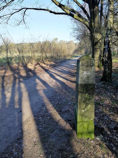 Grenzstein. Links verläuft der Weg auf niederländischem Gebiet, rechts ist Deutschland.