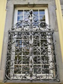 Aufwändig verzierte Gitter vor den Fensterflügeln im Hauptgebäude