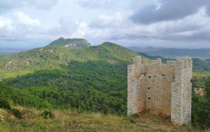 Reste eines alten Festungsturms mit dem Kloster Sant Salvador im Hintergrund