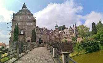 Blick durch das Schlosstor auf die Zufahrt zum Schloss