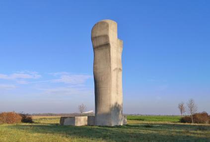 """Der Turm """"Begiari"""" des baskischen Bildhauers Eduardo Chillida (von 2001) mit Blick zur Skihalle Neuss und der Skyline von Düsseldorf im Hintergrund"""