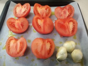 6. Arrange halved tomatoes and whole garlic cloves dipped in evoo on pan. Roast for 30 minutes