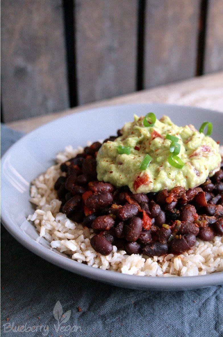 Sättigende Burrito Bowl mit Reis, schwarzen Bohnen und Guacamole