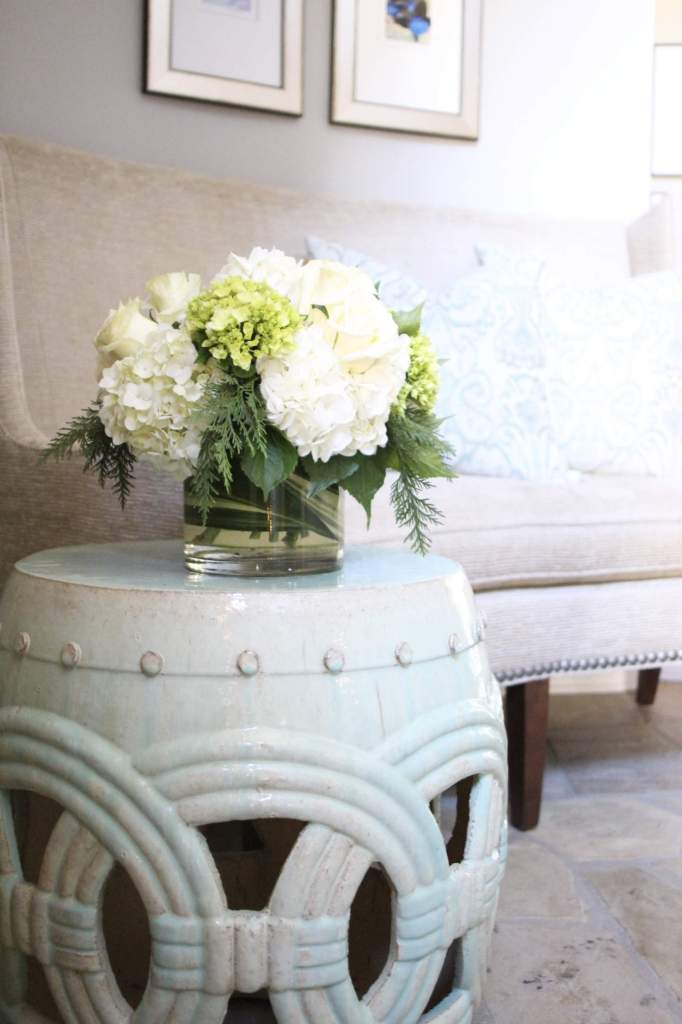 Mint green double coin garden stool for foyer entry table. Decorated with white hydrangea bouquet.
