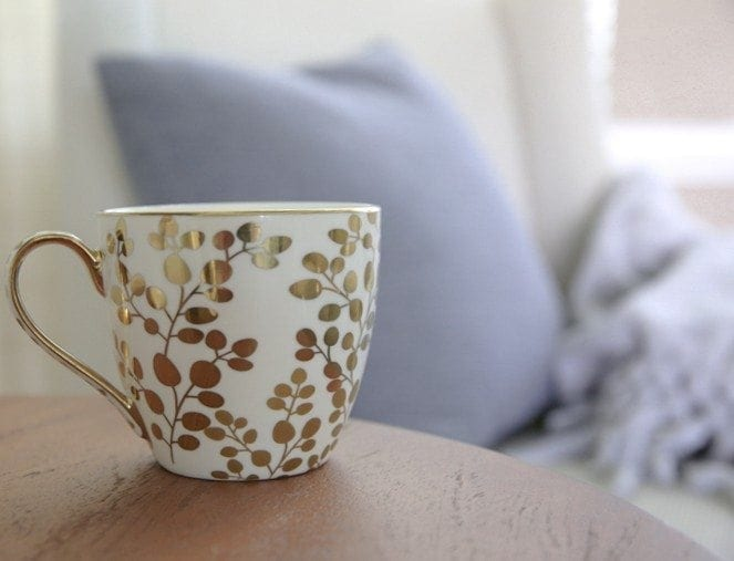 gold and white coffee mug with blue pillows