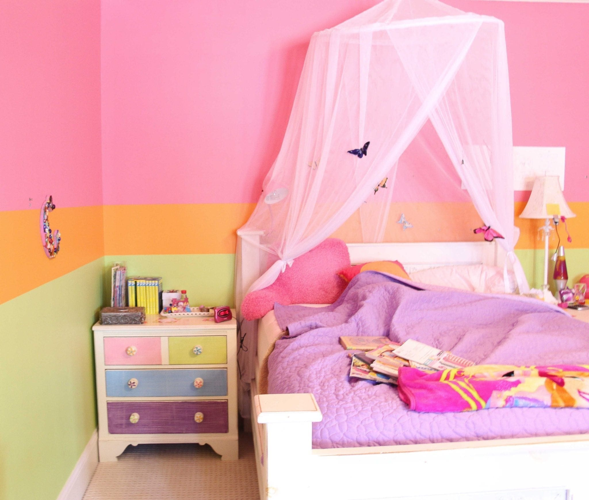 hot pink girls bedroom with hand painted nightstand next to a bed with a canopy