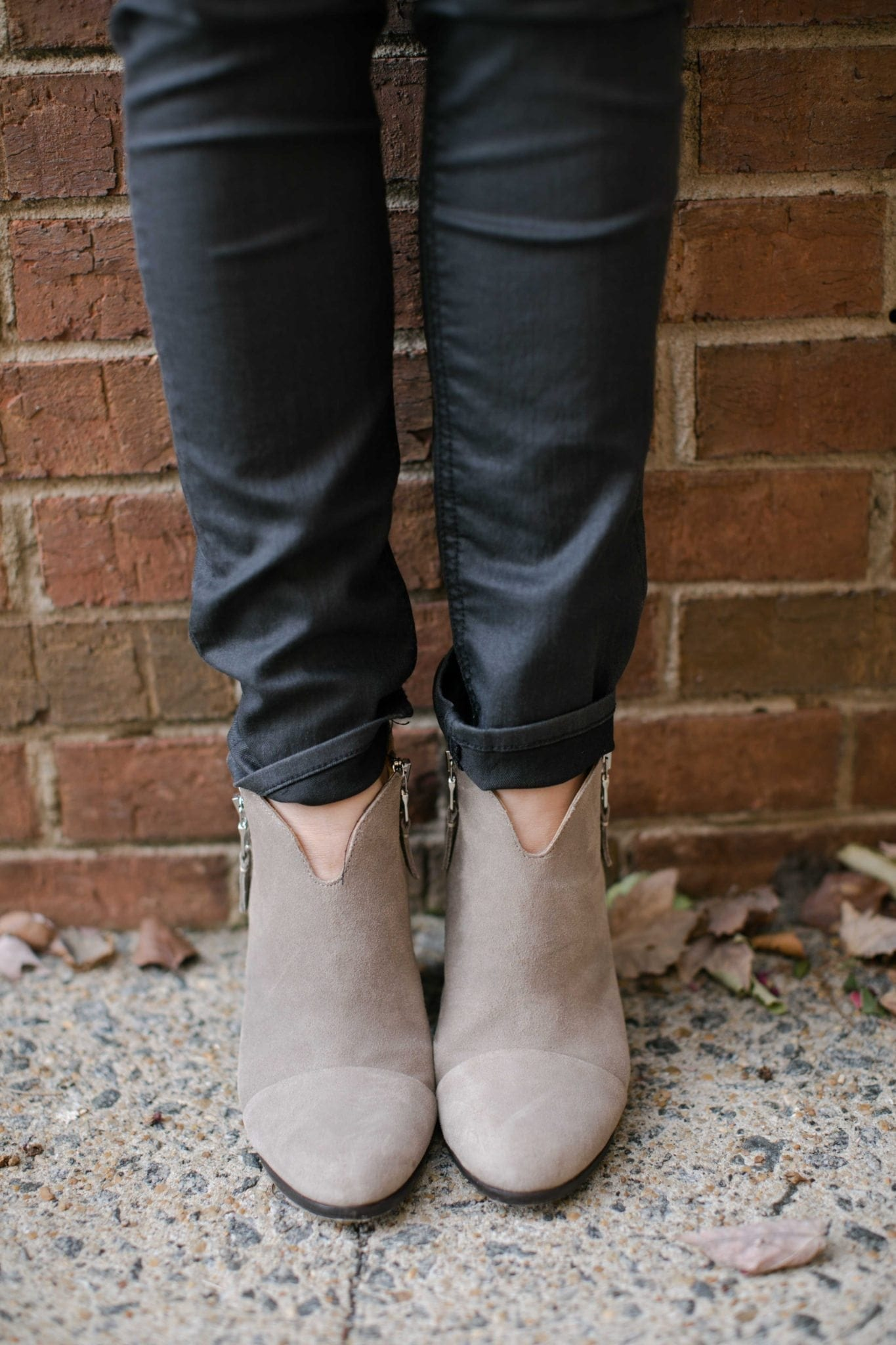 suede booties standing by leaves and brick wall