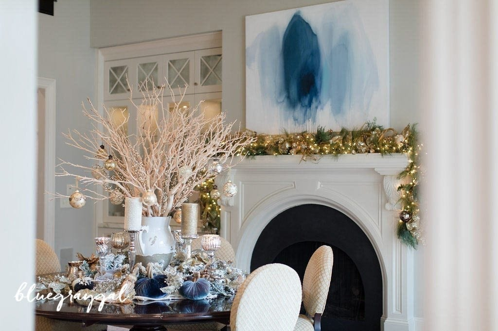 manzanita branches with christmas ornaments and flocked garland around it in a dining room with blue wall art