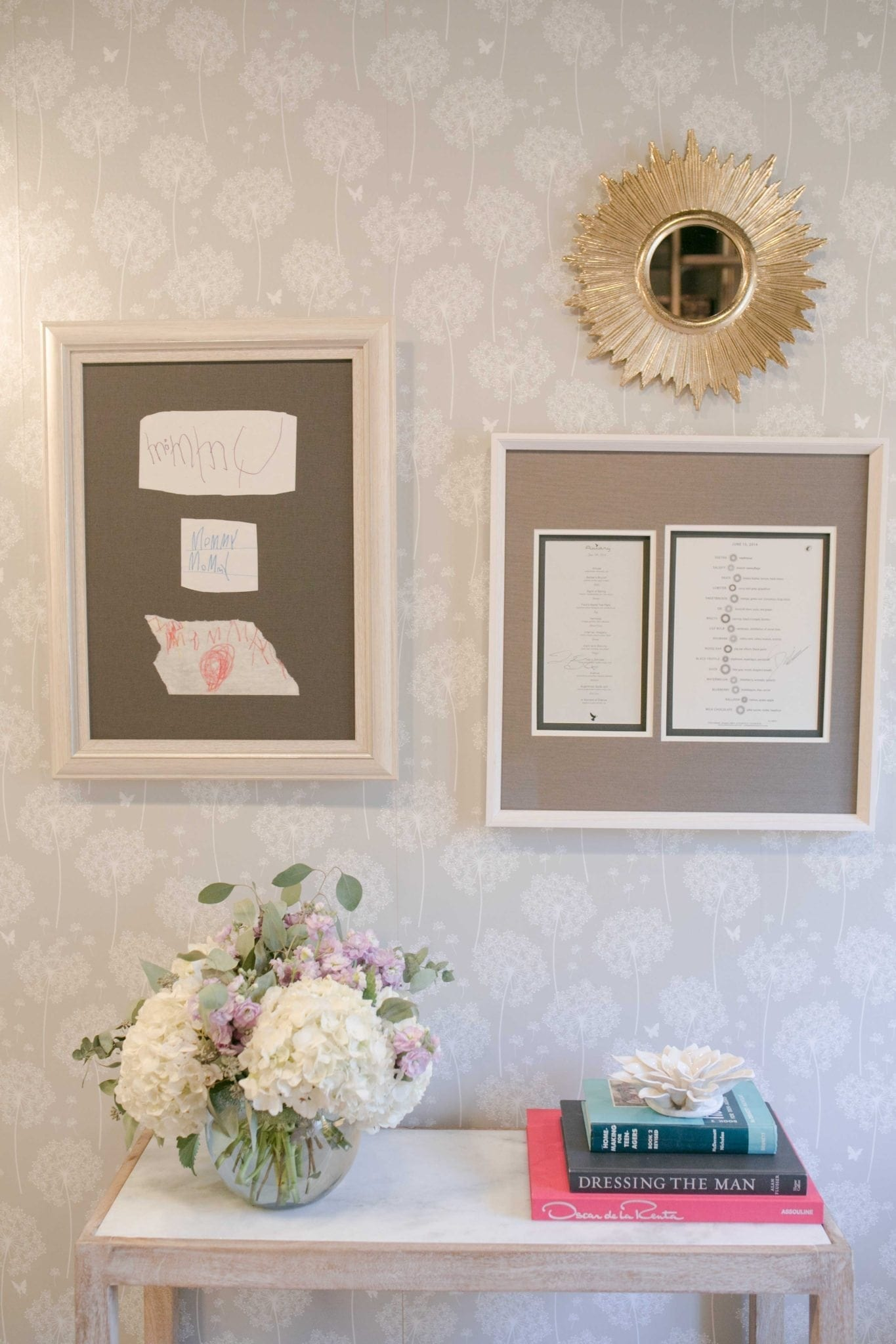 Wall pops wallpaper dandelion wallpaper hung with personal art and a gold starburst mirror and hydrangea floral arrangement on a white console table