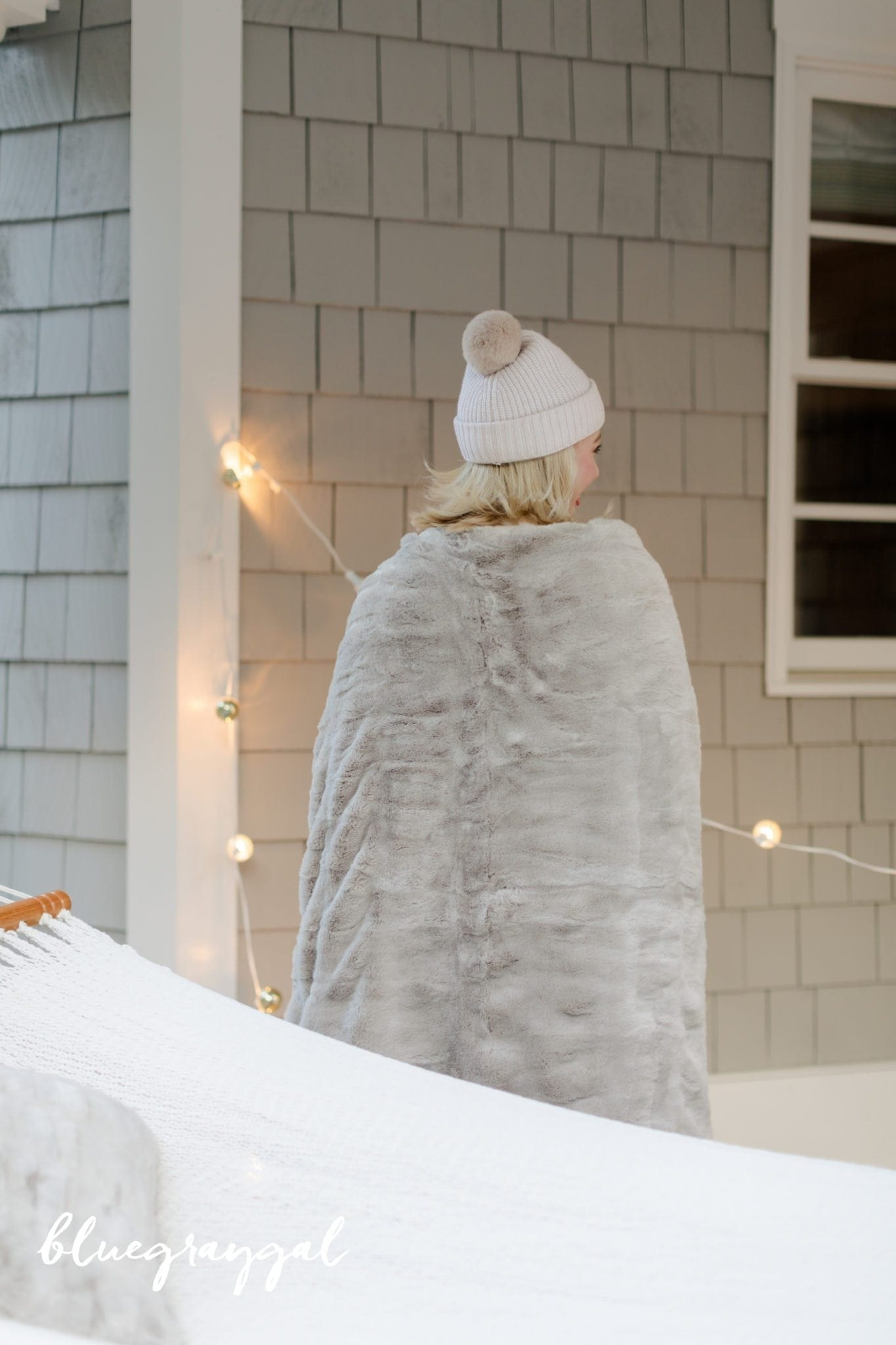 gray faux fur blanket wrapped around kelly page in a pink pom pom hat by gray shingle house exterior
