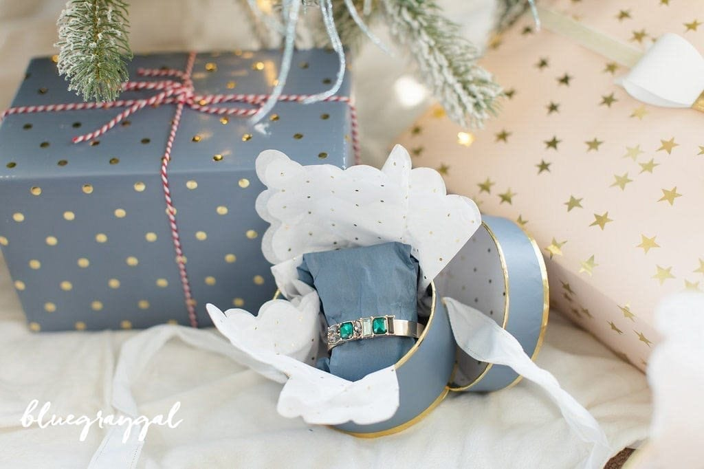 blue and gold wrapping paper with emerald gold bracelet in blue gift box