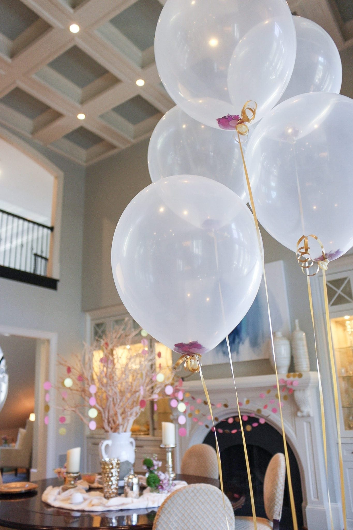 pink party ideas with balloons filled with glitter and pink mantel decor for a baby shower