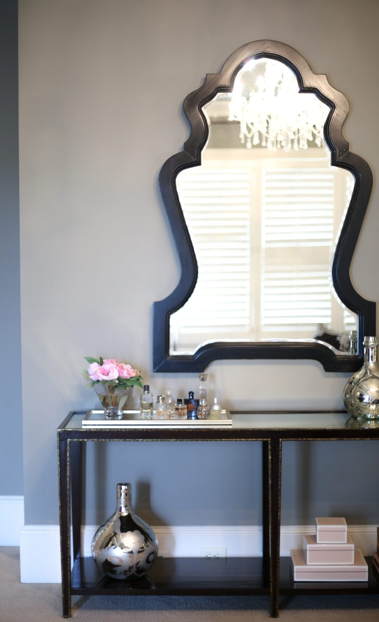Benjamin Moore dark gray paint on the walls of a bedroom decorated in gray, gold and black. Oversized large black framed mirror.