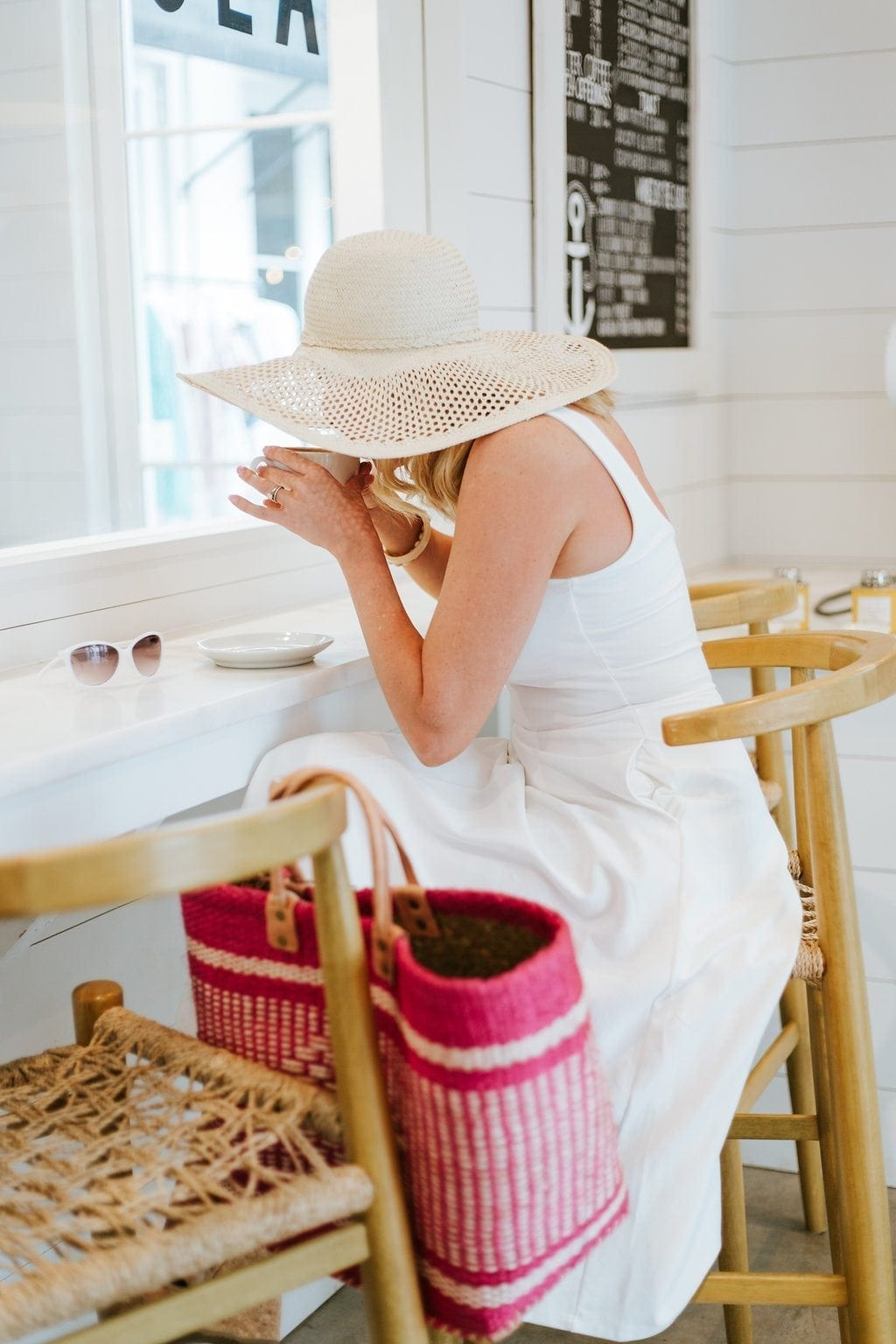 Sun hat and white summer dress. Drinking coffee in white coffee shop with shiplap walls and rattan bar chairs.