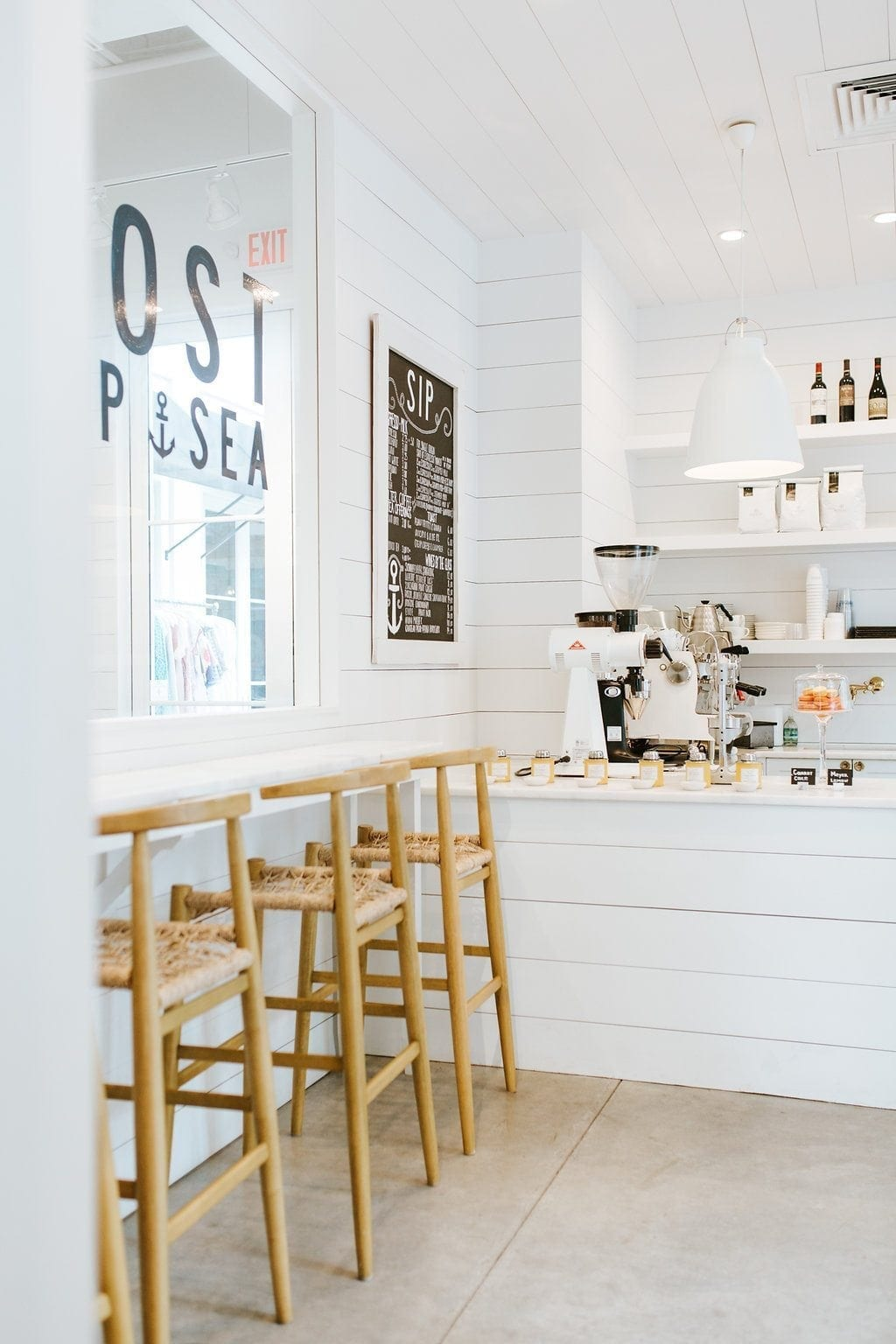 The Outpost Coffee Shop in Rosemary Beach. All white shiplap design coffee shop. This bright and happy coffee shop has character and fun. I love the design of the white bar counter and all white shelving with white lighting.