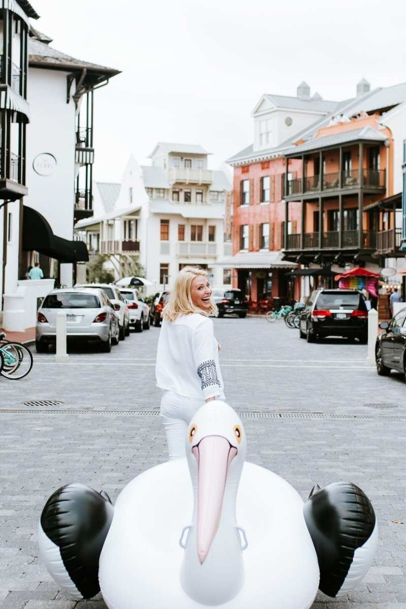 Atlanta Lifestyle Blogger Kelly Page dragging Sir Pelican the giant raft down streets of Rosemary Beach.