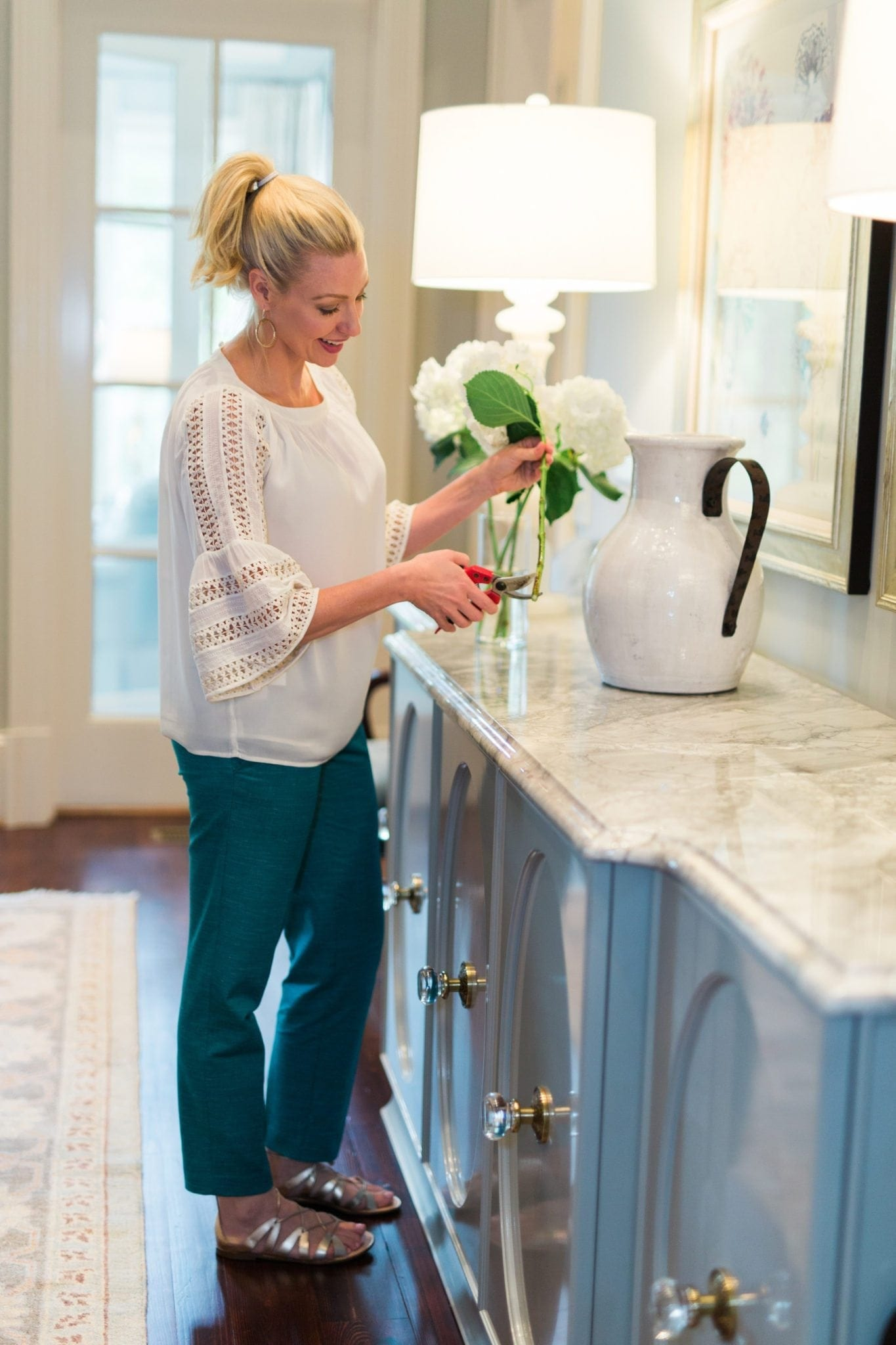 Spring outfit for women with teal pants and white lace top. Learn how to care for flower arrangements to keep them alive longer. White hydrangea and white tuscan urn on marble custom dining room table buffet.