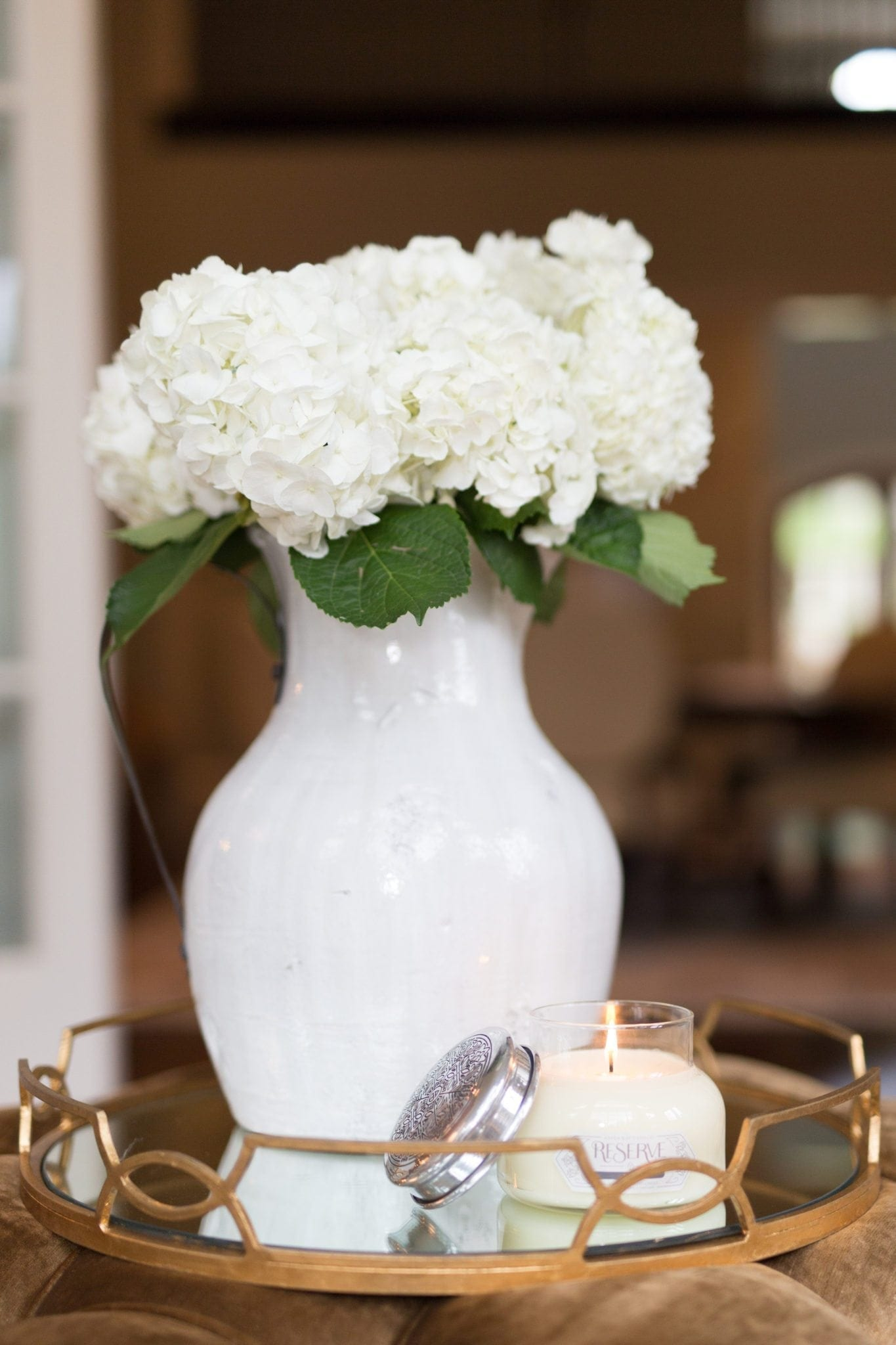 Learn to keep flower arrangements fresh. White ceramic urn from Pottery Barn filled with white hydrangea. Tricks to keep flowers alive longer.
