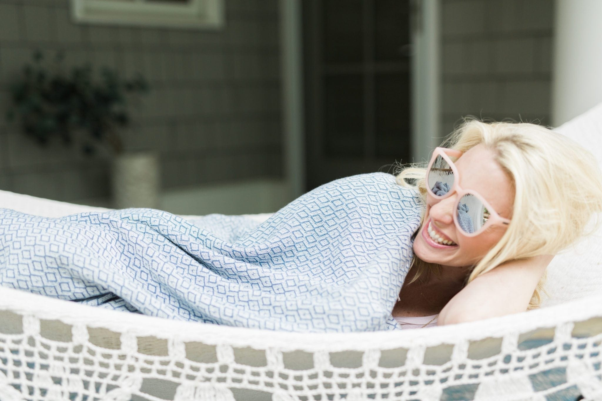 Oversized Mirrored Sunglasses are an outfit alone! Wear them with loungewear and look cute in minutes! Oversized pink sunglasses for women and a blue outdoor throw blanket on a fringe hammock say summer living everywhere!