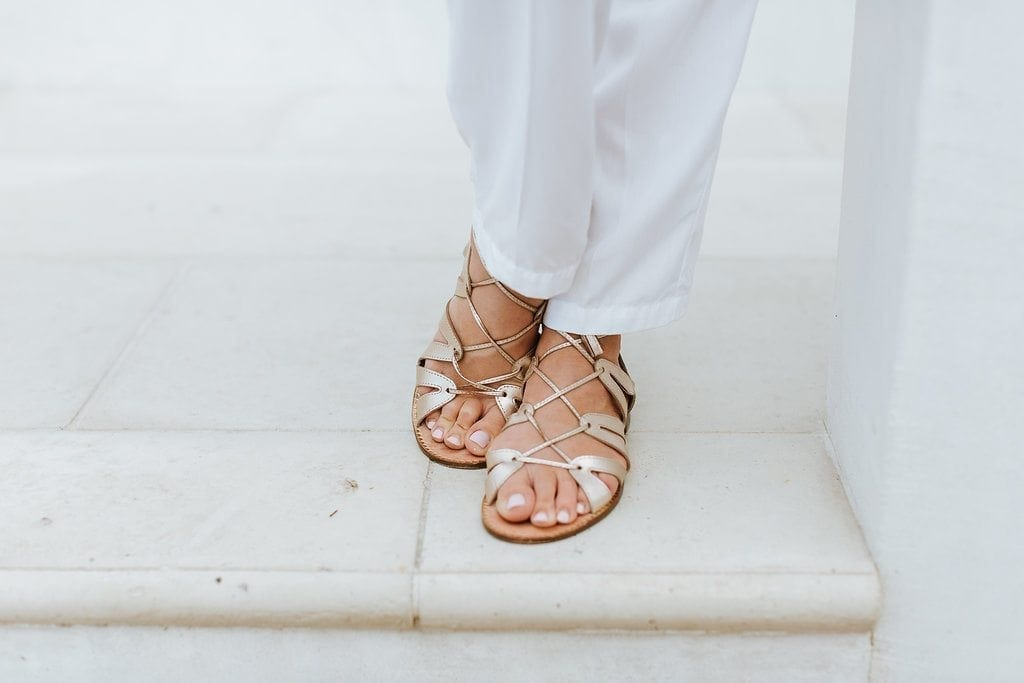 White and gold outfit ideas. Gold Gladiator sandals made by Lilly Pulitzer. Lilly Pulitzer summer sandals with white pants.