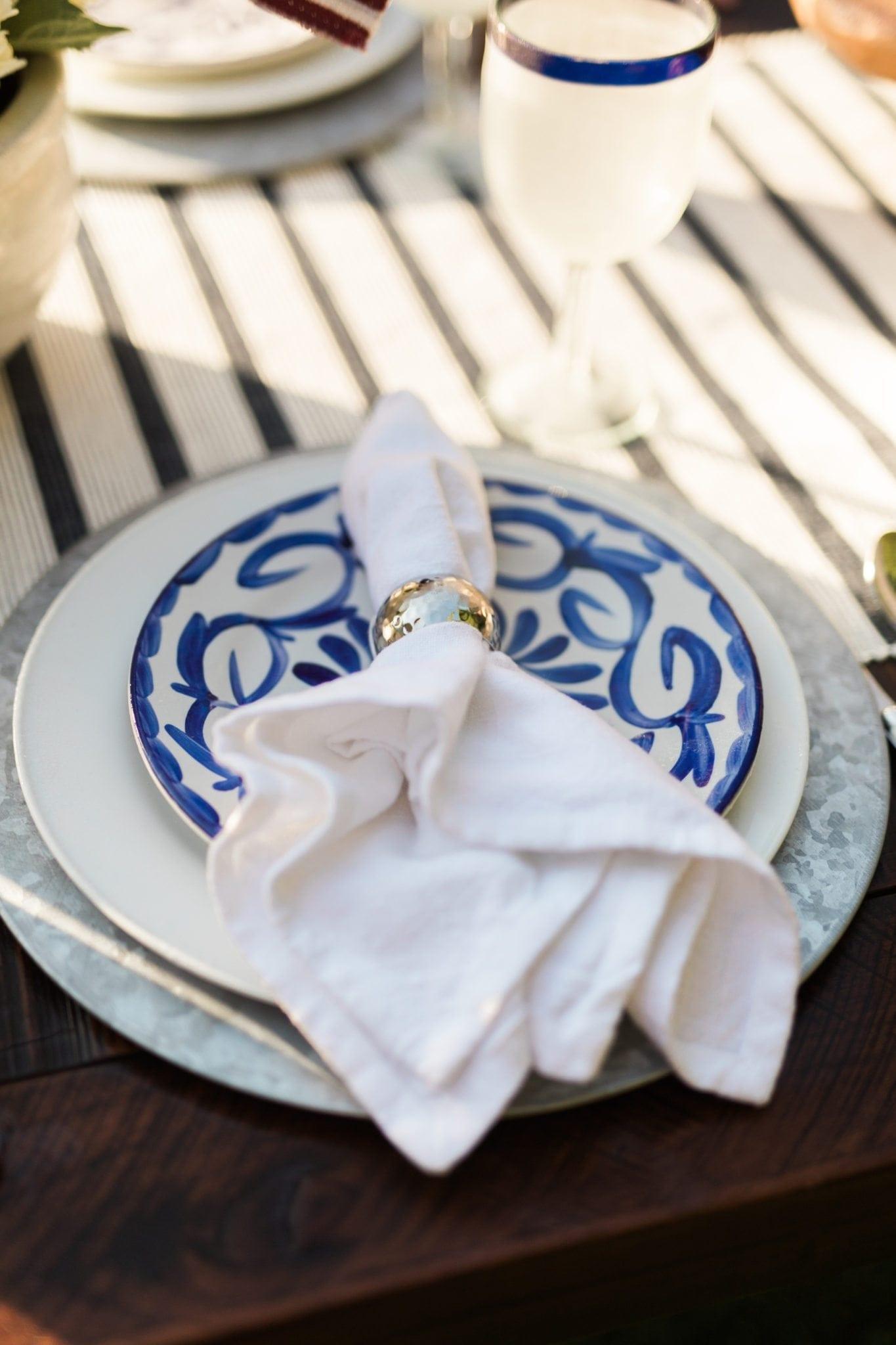 Blue and white dishware. White linen napkin and silver napkin ring.