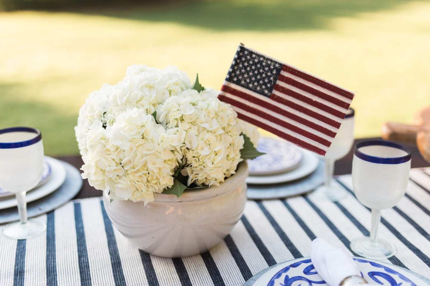 Patriotic decorations. July 4th centerpiece with white hydrangeas and American flag flower display.