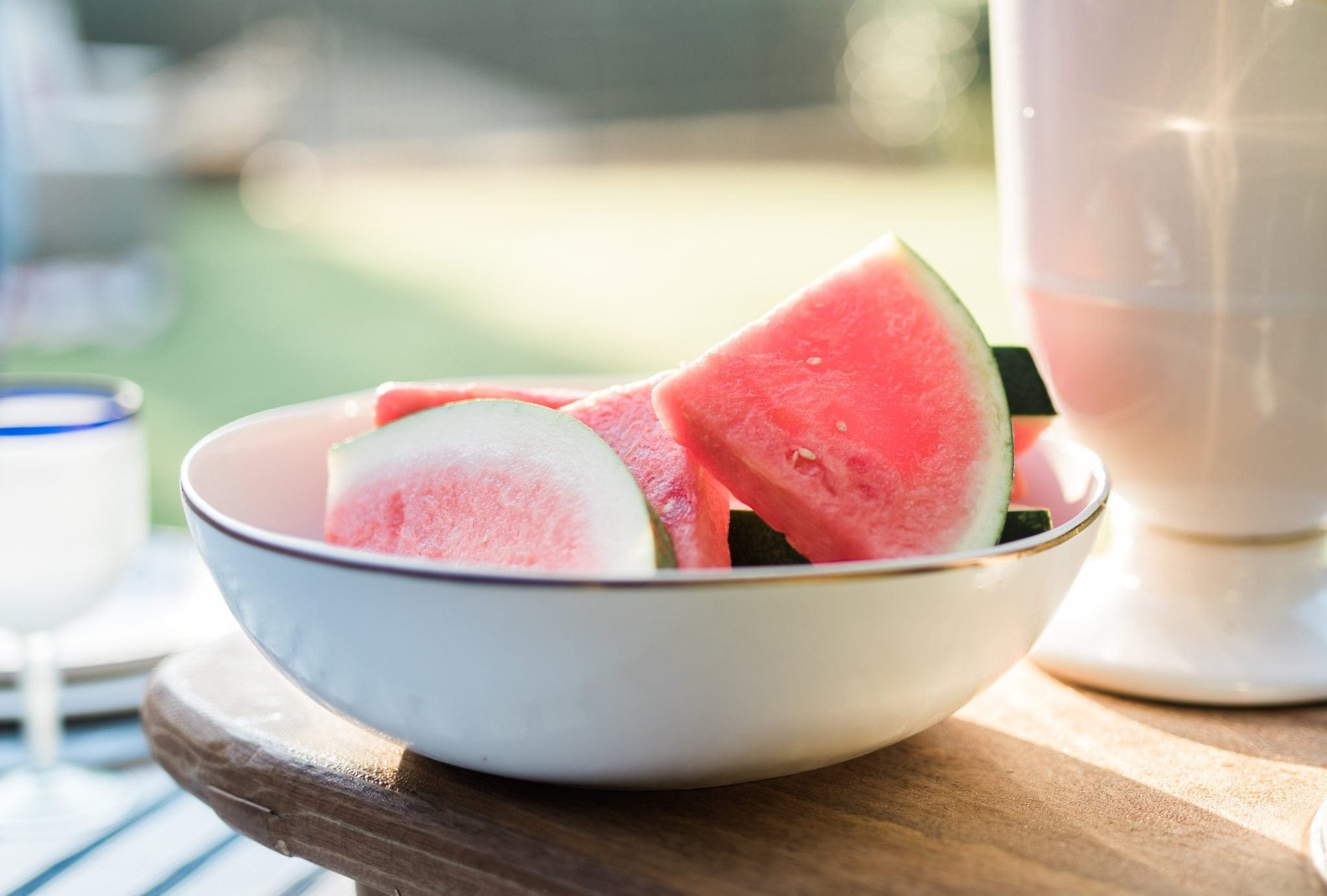Sliced watermelon in white bowl with gold rim.
