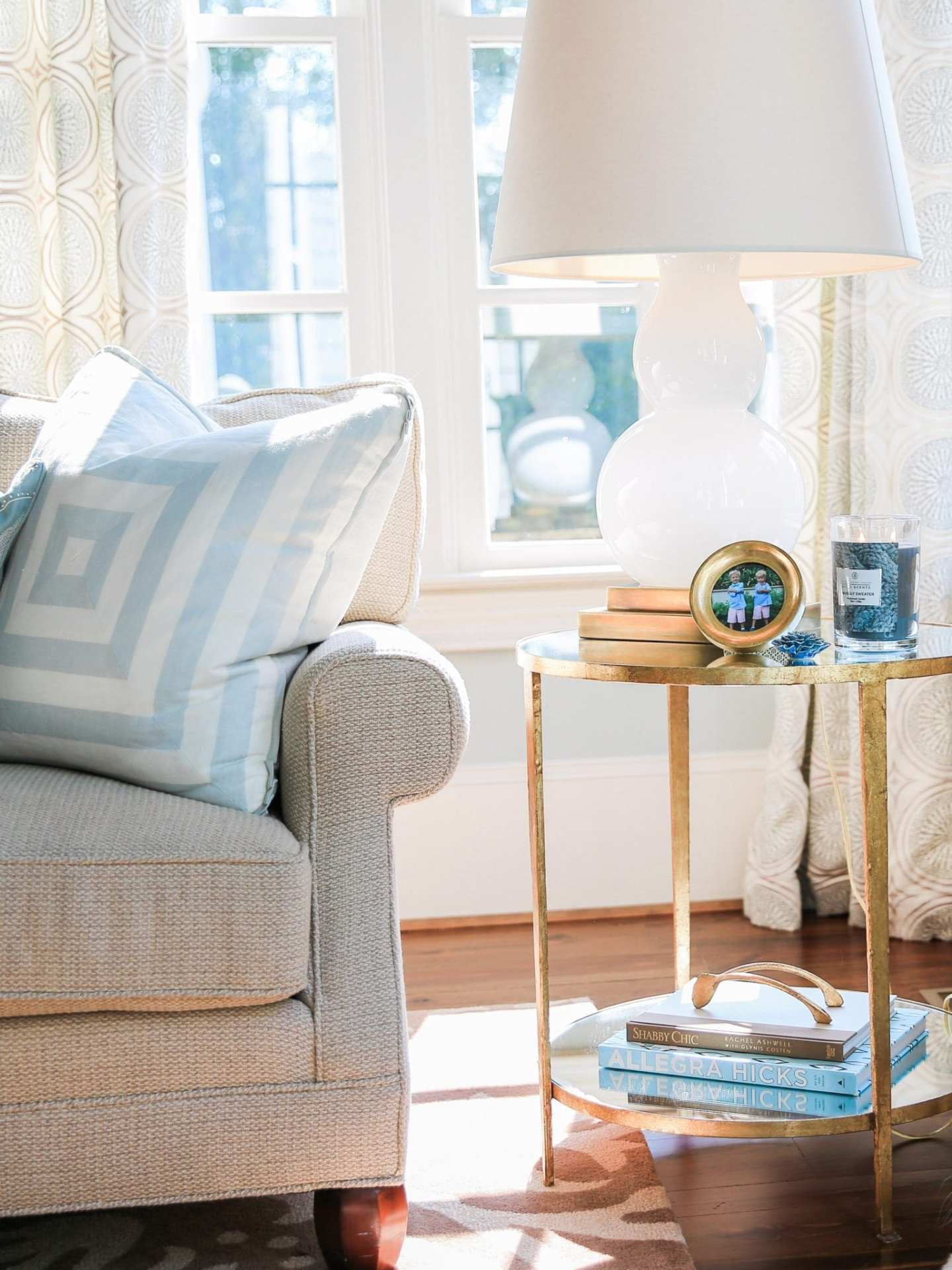 Blue and beige family room home decor with Chesapeake Bay Candle on gold end table.