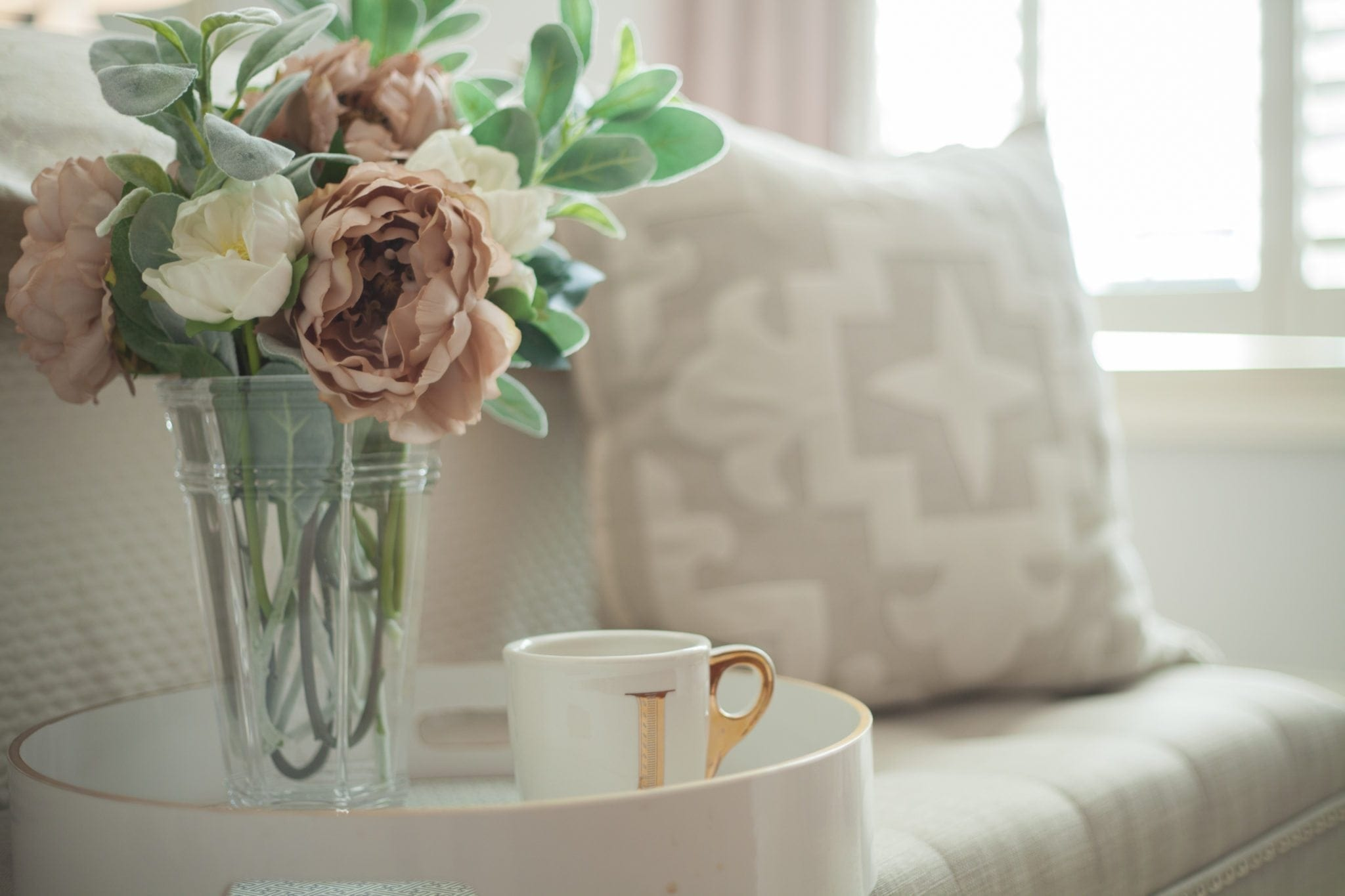 Silk flowers with neutral white and cream pillow with Anthropologie mug.