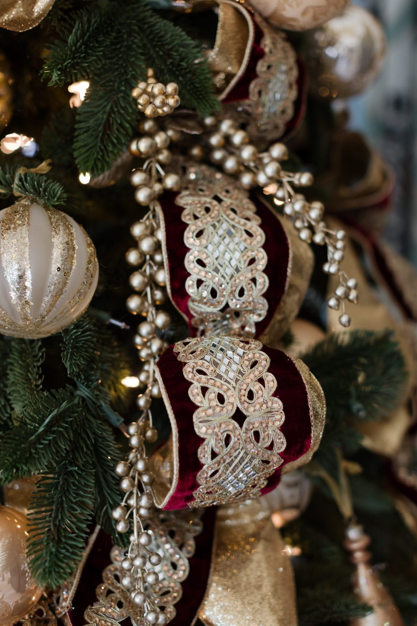 Gold tree picks mixed in with gold Christmas ornaments. Burgundy and gold christmas tree ideas.