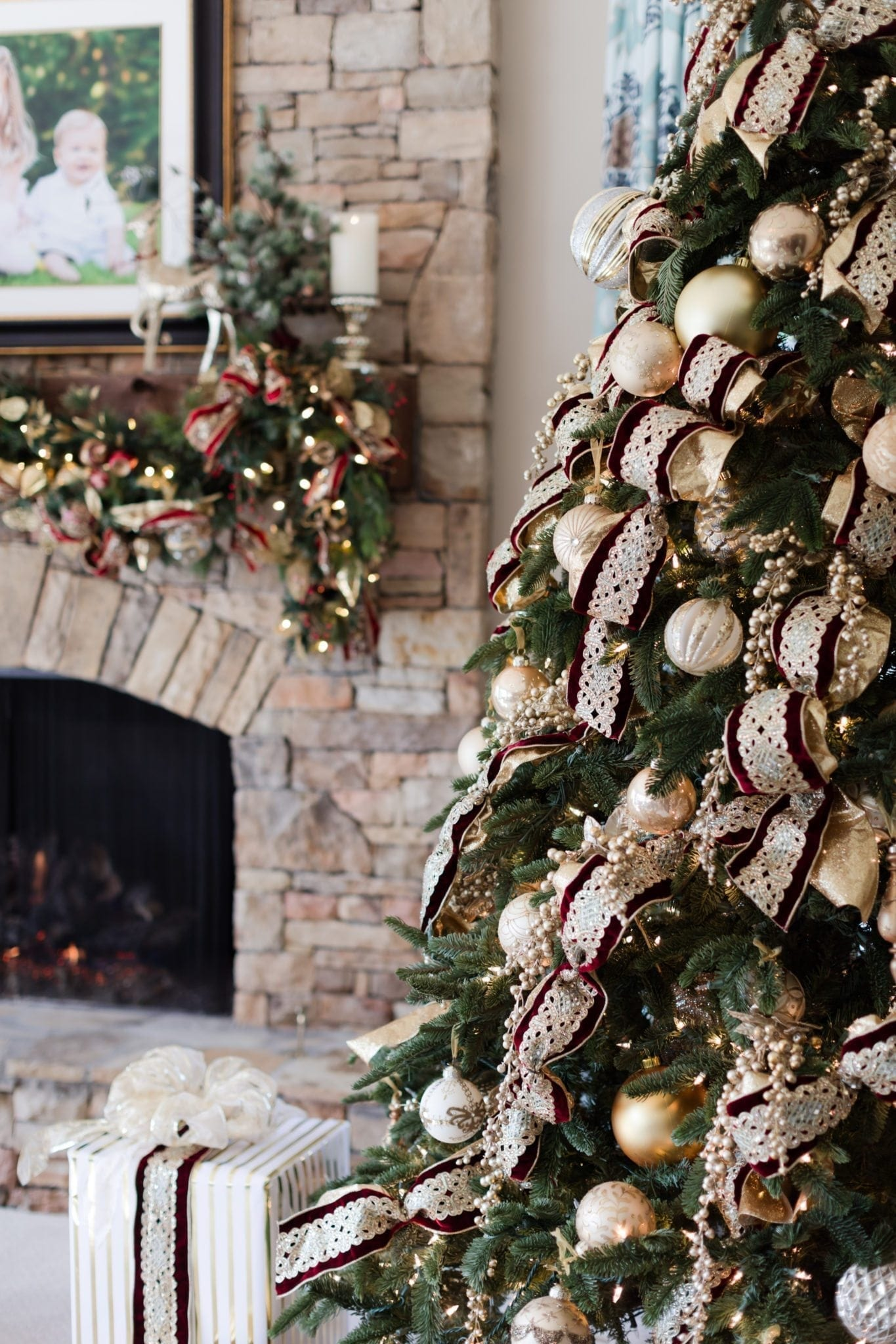 Stone fireplace with Christmas decor on mantle. Frontgate artificial tree with gold and red decorations.