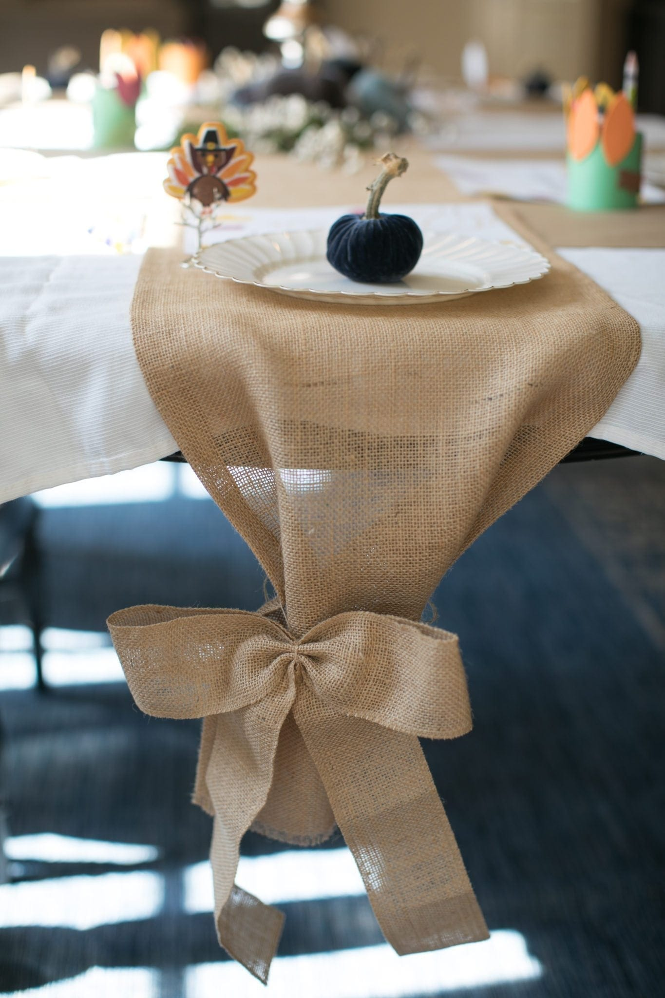Kids thanksgiving table with burlap bow and pumpkin placesetting.