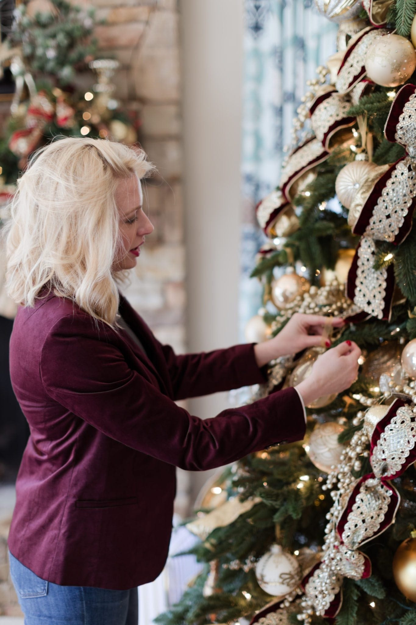 Decorating a Christmas tree in red velvet blazer and jeans.