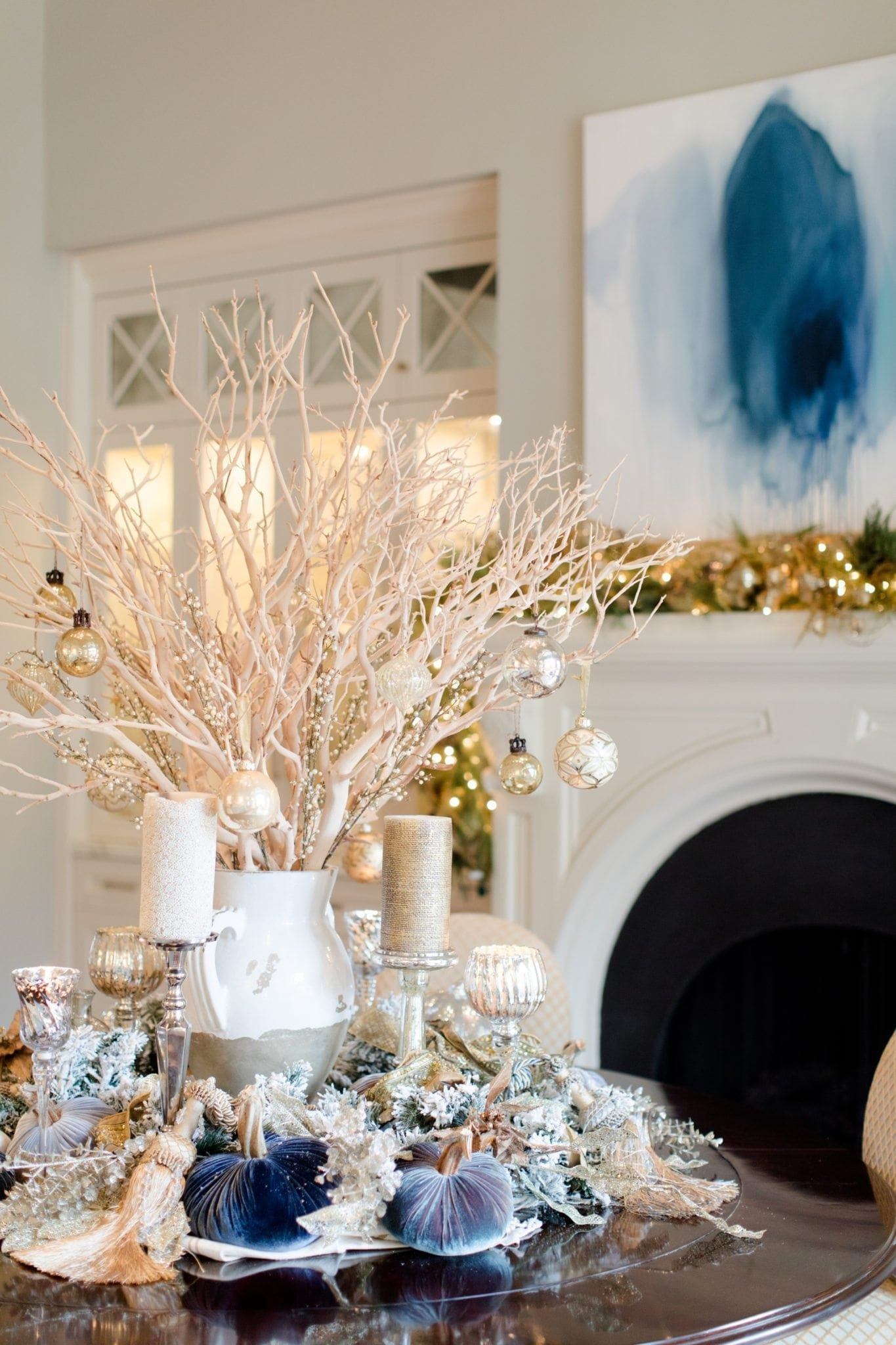 Christmas centerpiece idea. Manzanita branch centerpiece with ornaments hanging from them on a round dinner table.