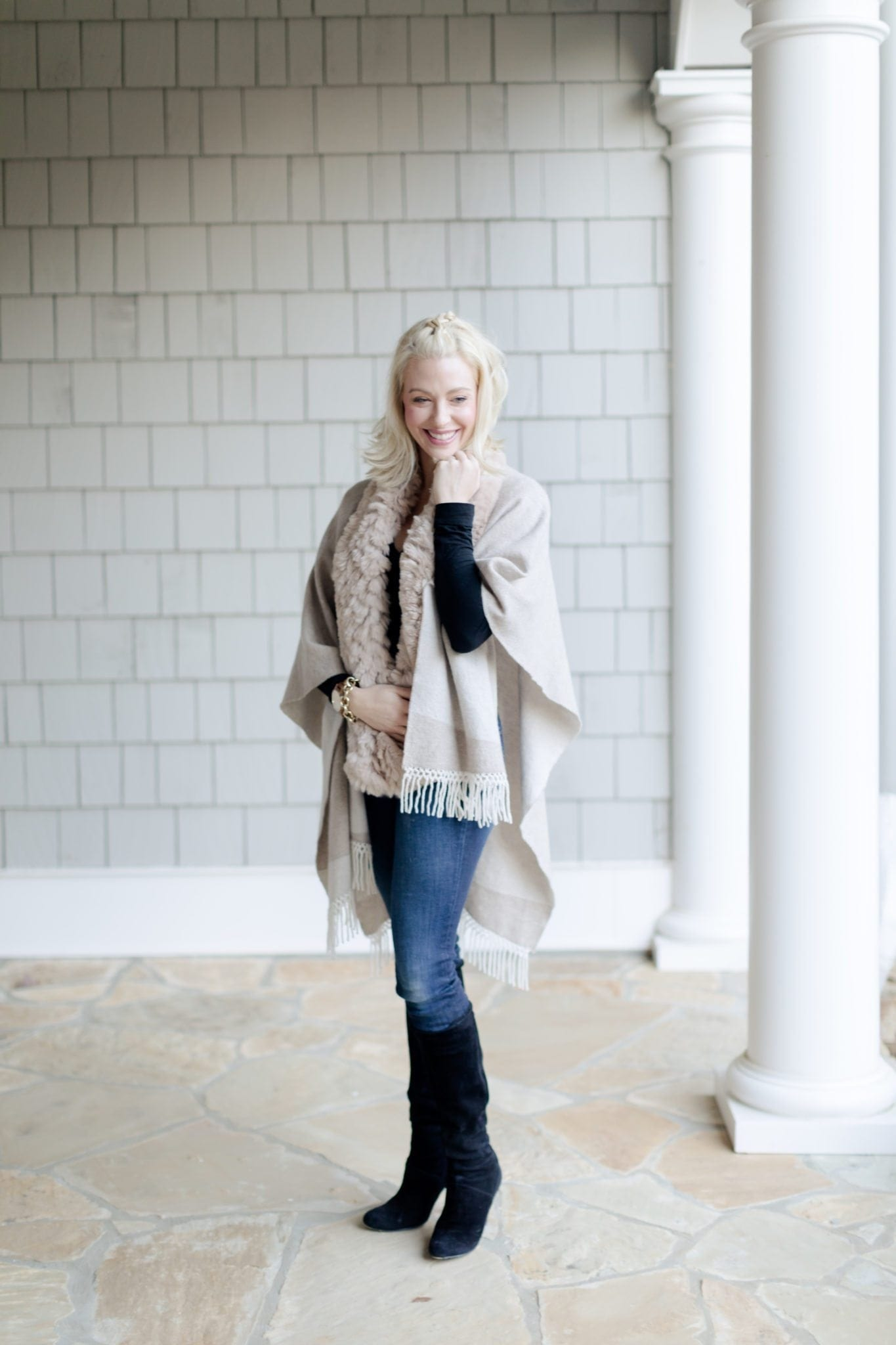 Knee High suede black boots with heel and tan cape and scarf. Short blonde hairstyle.