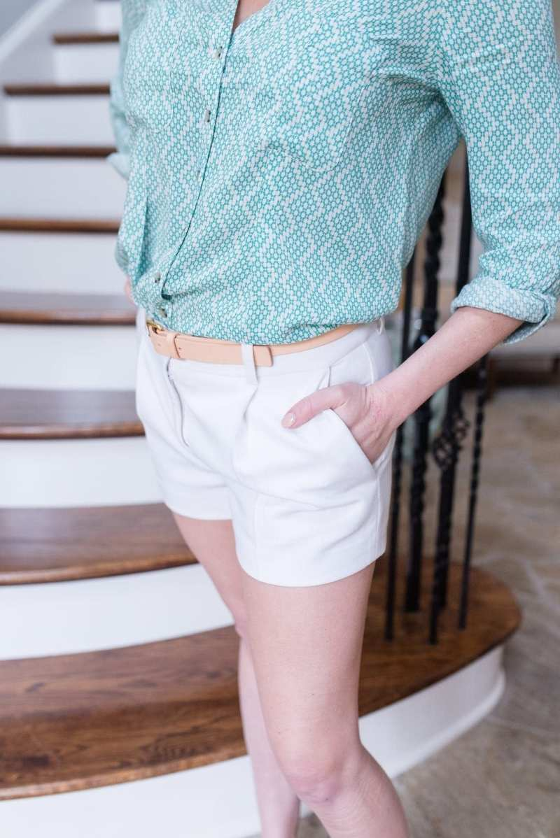 Women White shorts with coral belt and spring shirt.