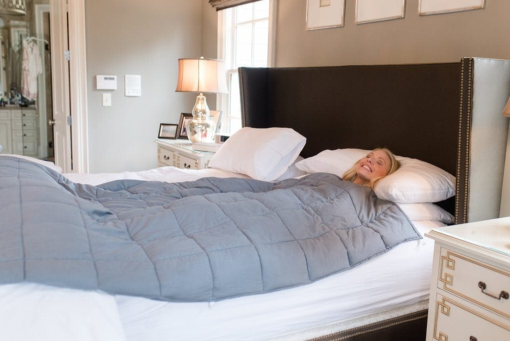 What are weighted blankets used for. Blue blanket on white bed for better sleeping.