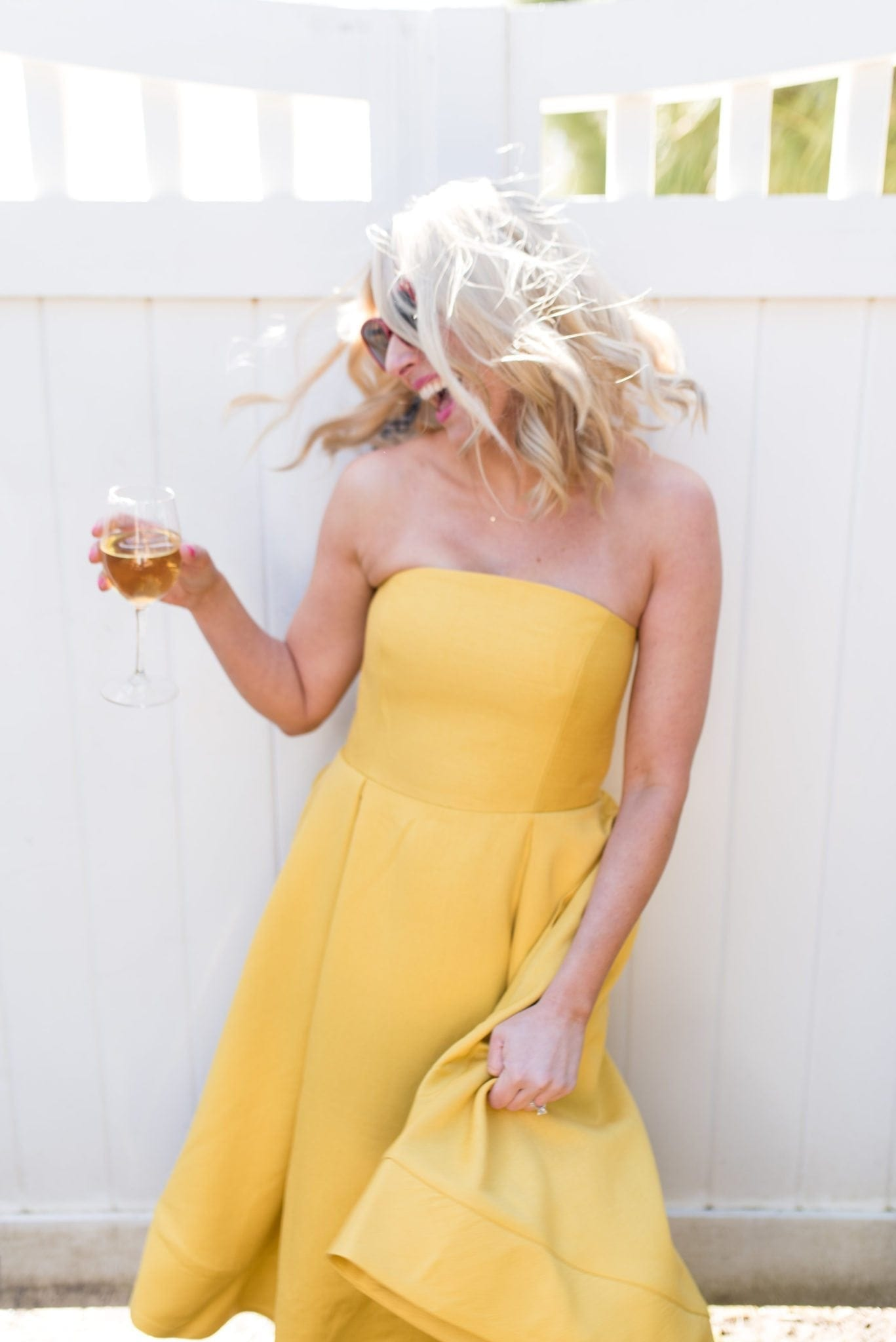 Strapless Yellow dress with full skirt. Red sunglasses.