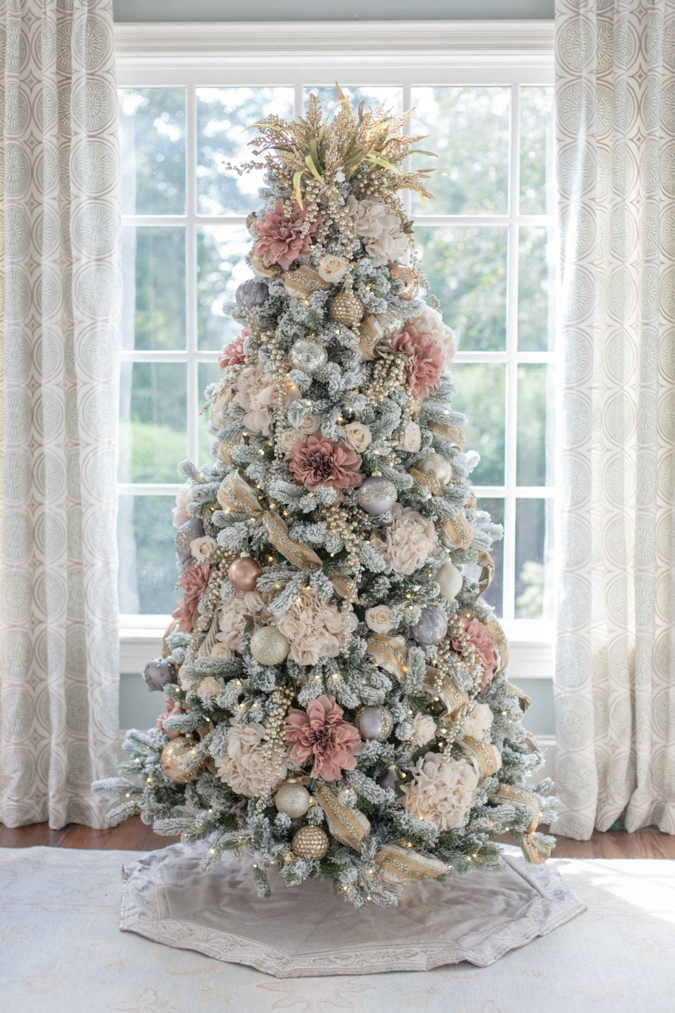 Pink and Gold Christmas Tree. A Christmas tree decorated with fake flowers. Rustic dried heather makes a unique Christmas tree topper and this King of Christmas flocked Christmas tree looks stunning. A non-traditional Christmas tree color! More how to decorate Christmas tree posts coming very soon!