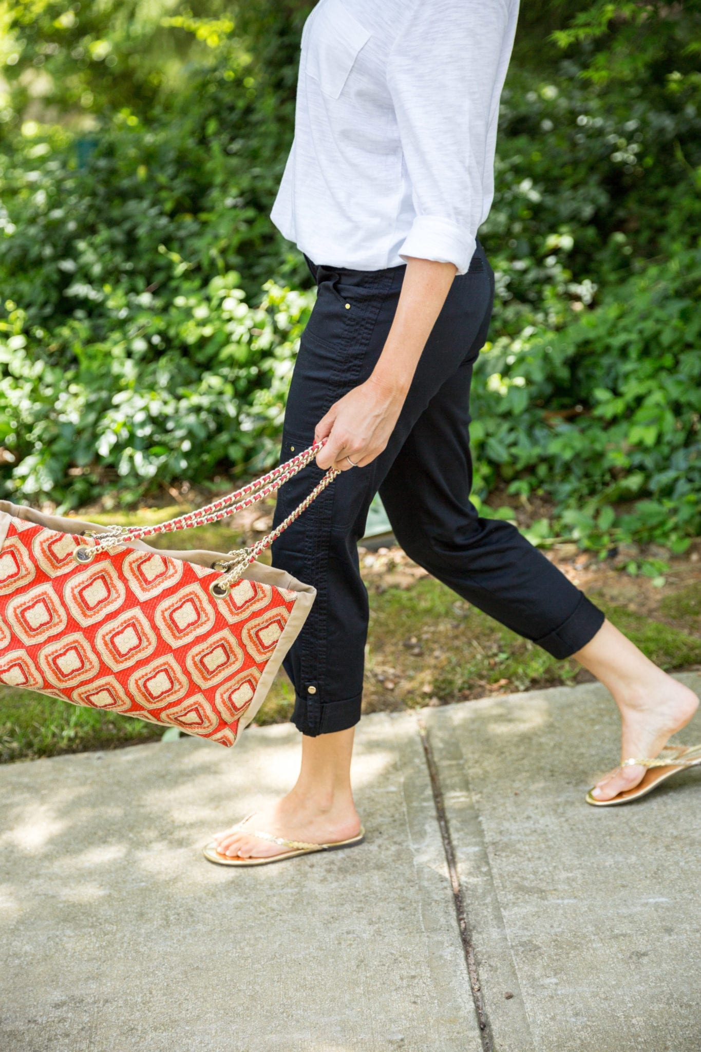 Orange and yellow beaded handbag from Chicos on sale. Black utility pants with gold button detail.